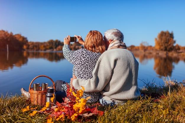 Pares superiores que tomam o selfie ao ter o piquenique pelo lago do outono.