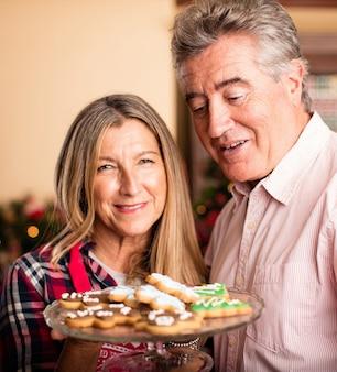 Pares velhos com uma bandeja de bolinhos do natal