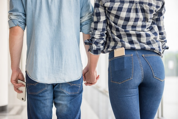 Pares vestidos ocasional que mantêm as mãos unidas.