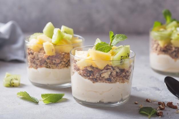 Parfait de iogurte caseiro com granola, kiwi, abacaxi e nozes em um copo no café da manhã saudável em fundo de concreto