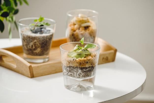 Parfait de iogurte de frutas com sementes de granola e chia no café da manhã saudável na mesa de madeira