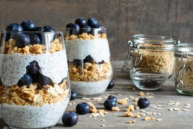 Parfait de iogurte de mirtilo com granola e sementes de chia em copos