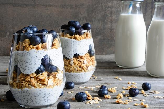 Parfait de iogurte de mirtilo com sementes de granola e chia e garrafas de leite