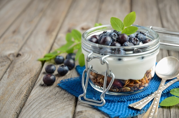 Parfait do iogurte com granola e os mirtilos frescos, conceito saudável do café da manhã.