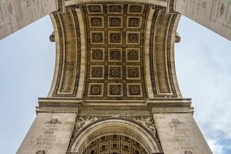 Paris Arc de Triomphe (arco triunfal) em rachaduras Elysees no céu nebuloso, Paris, França.