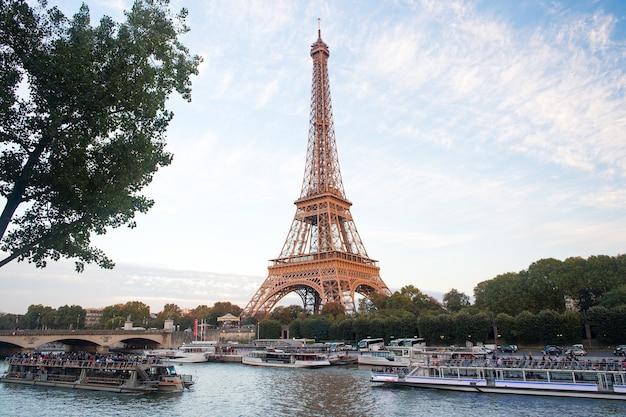 Paris, frança - 29 de setembro de 2017: cruzeiros no rio sena e a torre eiffel. passeios de barco. viagens à beira-mar. passeio turístico. viagem de paisagens e pontos de referência. viajar e viajar. férias de verão.