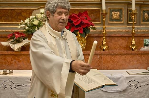 Pároco que entrega a vela aos pais durante o rito católico do baptismo.