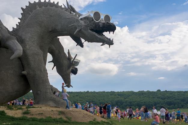 Parque com pessoas andando, festival de música, estátua da serpente gorynych