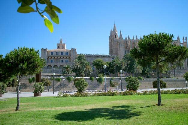 Parque com vegetação na cidade de palma de maiorca com um edifício antigo