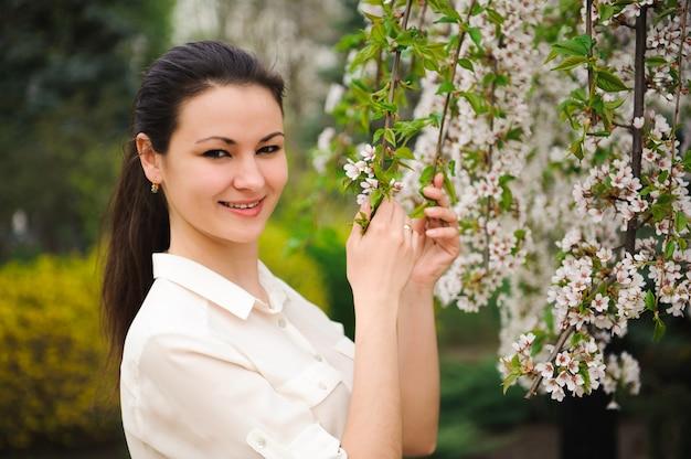 Parque da menina na primavera perto de uma árvore de florescência.