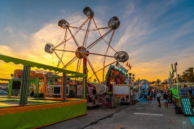 Parque de diversões ao pôr do sol na cidade costeira de torrevieja, alicante, comunidade valenciana. espanha, mar mediterrâneo