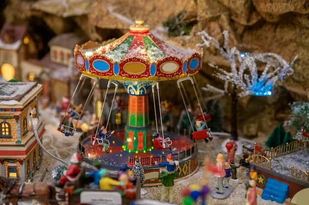 Parque de diversões em miniatura com carrosséis e estatuetas no inverno