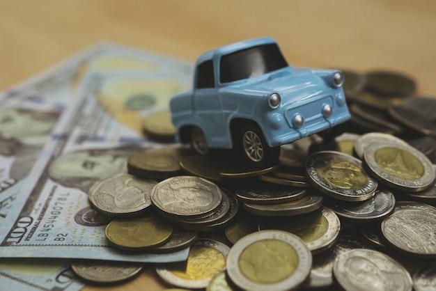 Parque de estacionamento de brinquedo de colarinho azul do céu modelo em moedas de pilha. modelo do carro na pilha de moedas. conceito de poupança, finanças, empréstimo e leasing.