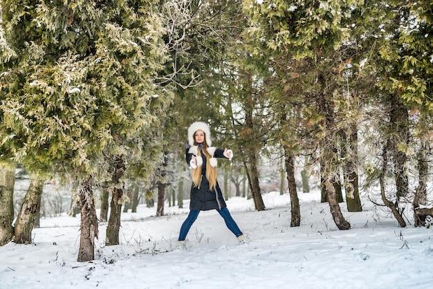 Parque de inverno com jovem entre árvores