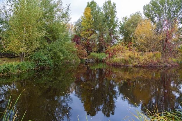 Parque do outono. árvores refletidas na água do lago do parque