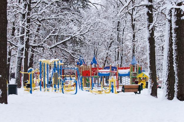 Parque infantil colorido vazio de crianças no quintal no parque no inverno frio snowly