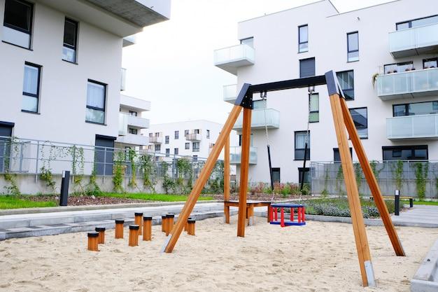 Parque infantil com um balanço de crianças no acolhedor pátio do moderno bairro residencial.