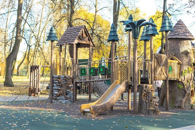 Parque infantil de madeira vazio ao ar livre com balanços na floresta no outono ao ar livre sem ninguém