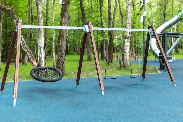 Parque infantil de madeira vazio ao ar livre com balanços na floresta no verão ao ar livre sem ninguém