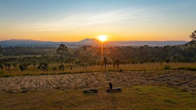 Parque nacional thung salaeng luang lindas colinas verdes brilhando com o nascer do sol quente, silhueta com brilho dramático