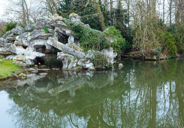 Parque primavera com reflexo de lagoa e árvores na superfície da água.