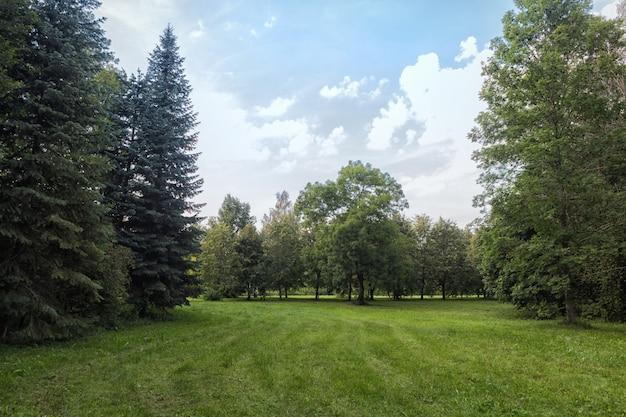 Parque velho com gramados verdes e árvores grandes.