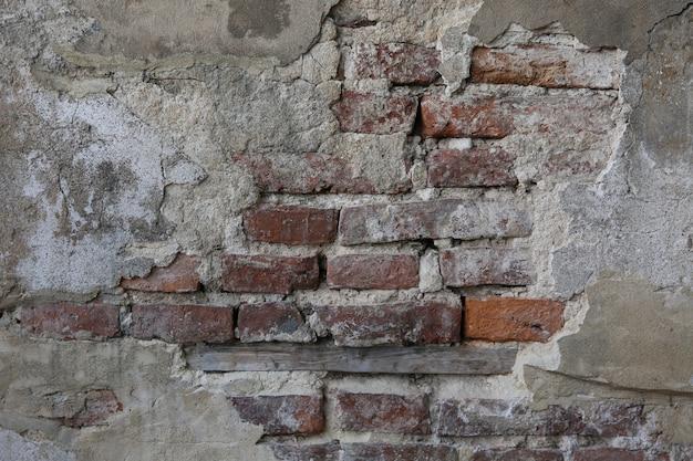 Parte abstrata da velha parede de tijolos com gesso arruinado para fundo vintage e papel de parede no estilo sépia