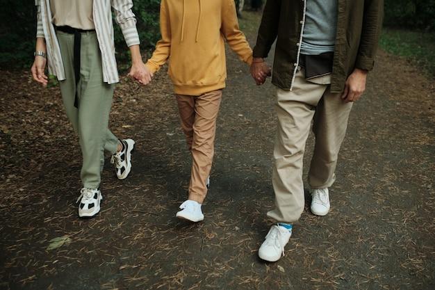 Parte baixa de uma família contemporânea de mãos dadas enquanto caminha pelo caminho da floresta ou estrada cercada por agulhas de coníferas no fim de semana