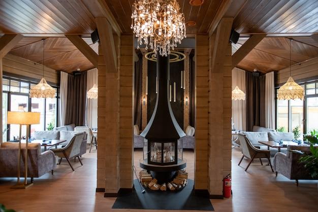 Parte central do interior de um restaurante moderno e luxuoso que parece uma pequena lareira com áreas de jantar para os hóspedes de ambos os lados