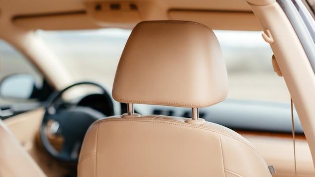 Parte da cadeira de couro amarela com o carro fora de foco