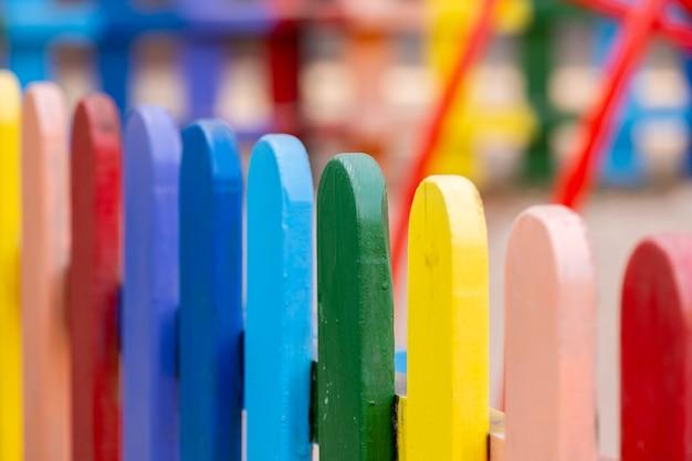Parte da cerca pintada colorida de madeira, arco-íris em um dia quente de verão ensolarado em um parque da cidade. plano de fundo multicolorido abstrato.