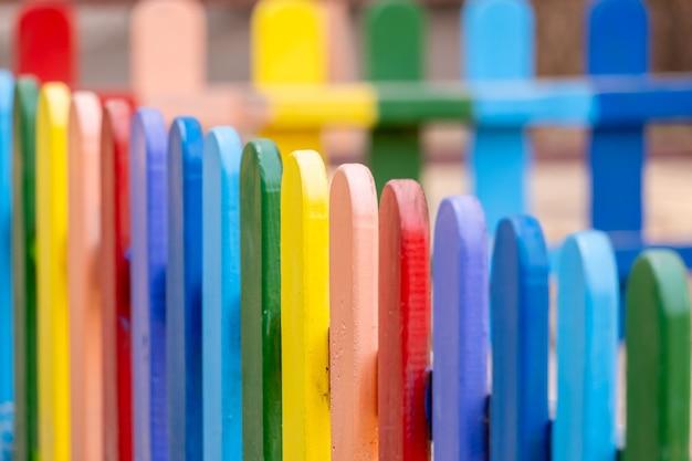 Parte da cerca pintada colorida de madeira, arco-íris em um dia quente de verão ensolarado em um parque da cidade.