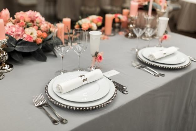 Parte da configuração de mesa elegante com prato e talheres. perto está um cartão de visita branco. copie o espaço