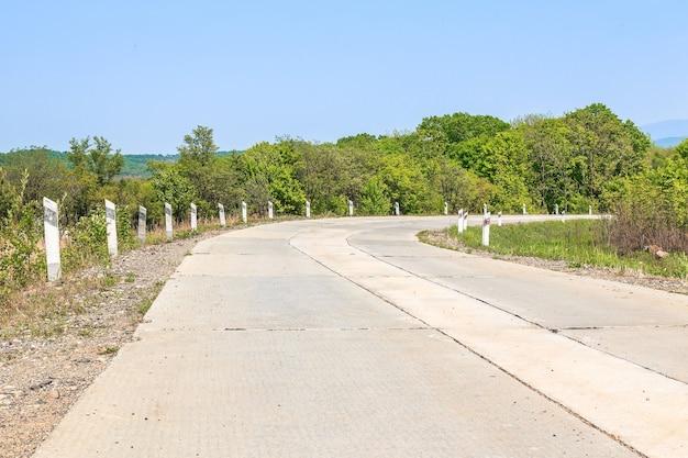 Parte da estrada secundária de lajes de concreto se transforma no contexto de árvores e arbustos de verão sob um céu brilhante de verão em um dia ensolarado.
