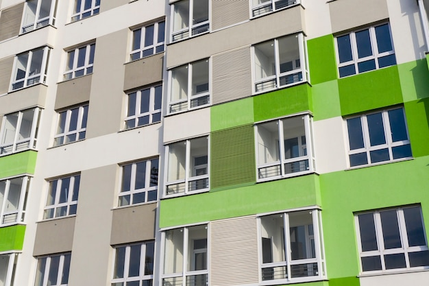 Parte da fachada com janelas de uma casa nova com paredes verdes acinzentadas