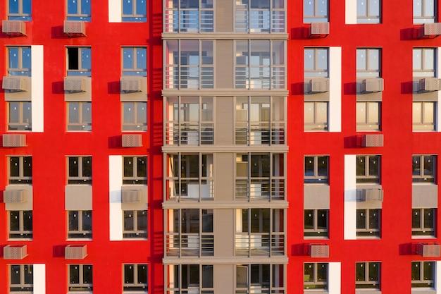 Parte da fachada com janelas de uma casa nova com paredes vermelhas