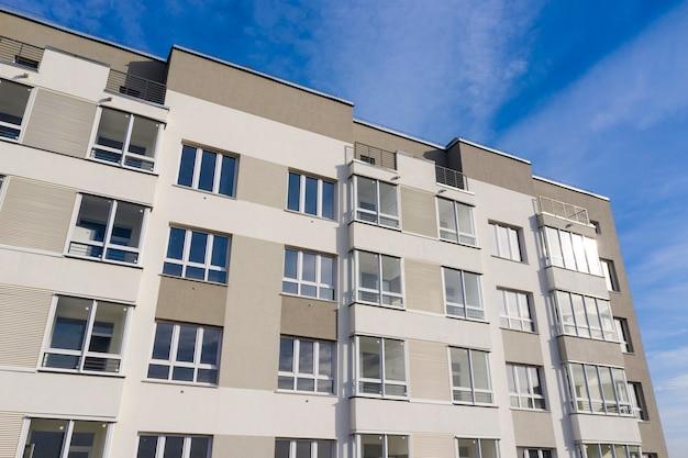 Parte da fachada verde-cinza com janelas contra o céu azul