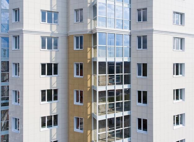 Parte da fachada verde-cinza com janelas