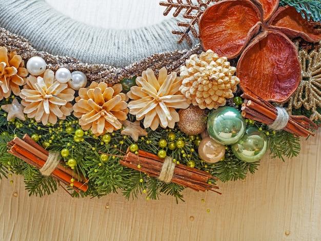 Parte da guirlanda de decoração de natal com cones e brinquedos de natal em fundo bege. close up shot