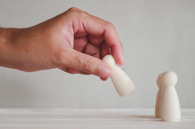 Parte da mão humana escolher um dos bonecos de madeira da linha