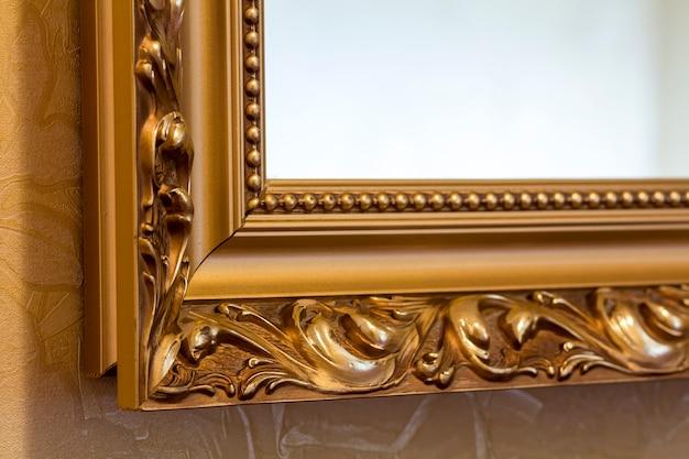 Parte da moldura de espelho esculpida em dourado e ornamentada em estilo antigo.