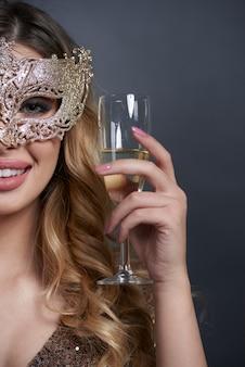 Parte da mulher com máscara fazendo um brinde
