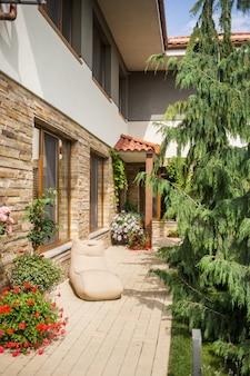Parte da parede de tijolos da casa e os vasos de flores com flores ao lado