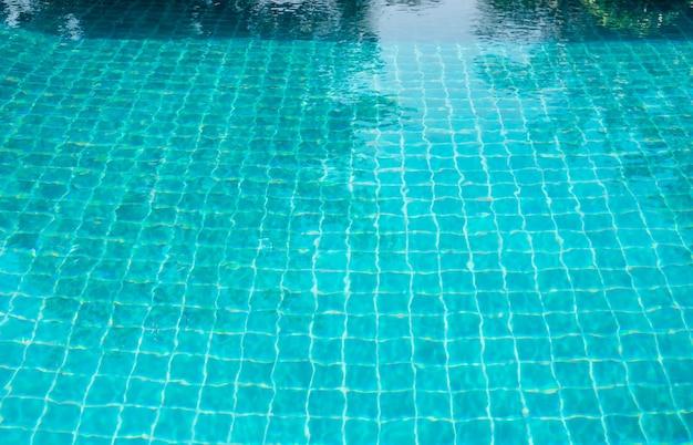 Parte da piscina e azulejo turquesa com água azul.