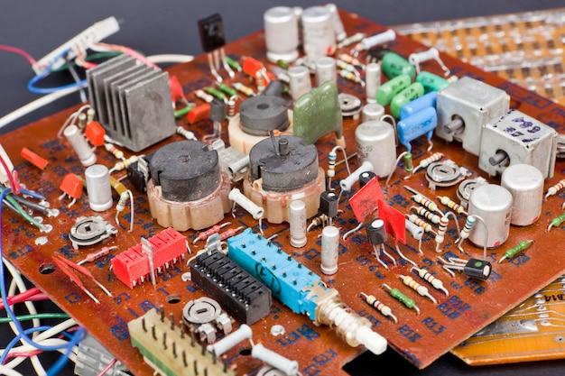 Parte da placa de circuito impresso velha do vintage com componentes eletrônicos.