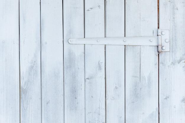 Parte da porta de madeira branca com dobradiças