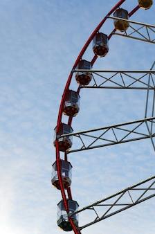 Parte da roda gigante com cabines no fundo de nuvens cirros e céu azul