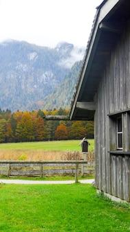 Parte da velha cabana de madeira com grama verde sobre fundo de montanha