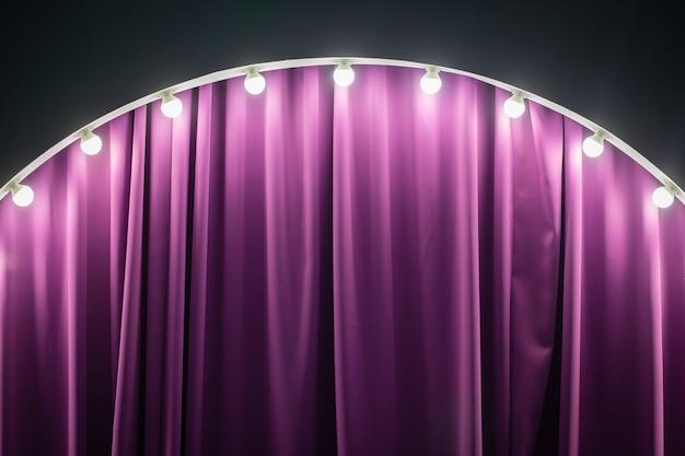 Parte da zona no palco, decorada com lâmpadas. bastidores roxos, iluminação forte.