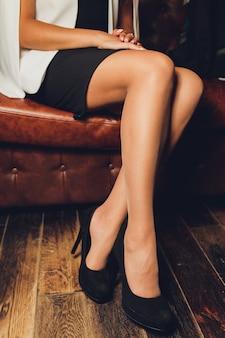 Parte de mulheres jovens com pernas perfeitas, mantendo as pernas cruzadas no joelho enquanto está sentado no sofá na loja de sapatos.